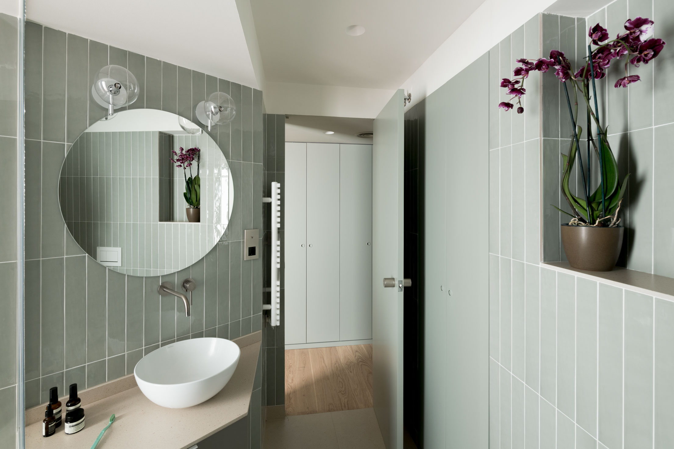 The bathroom is lined with vertical tiles, in the same sage grey-green colour as the wardrobe and it's designed to take advantage of irregularities.