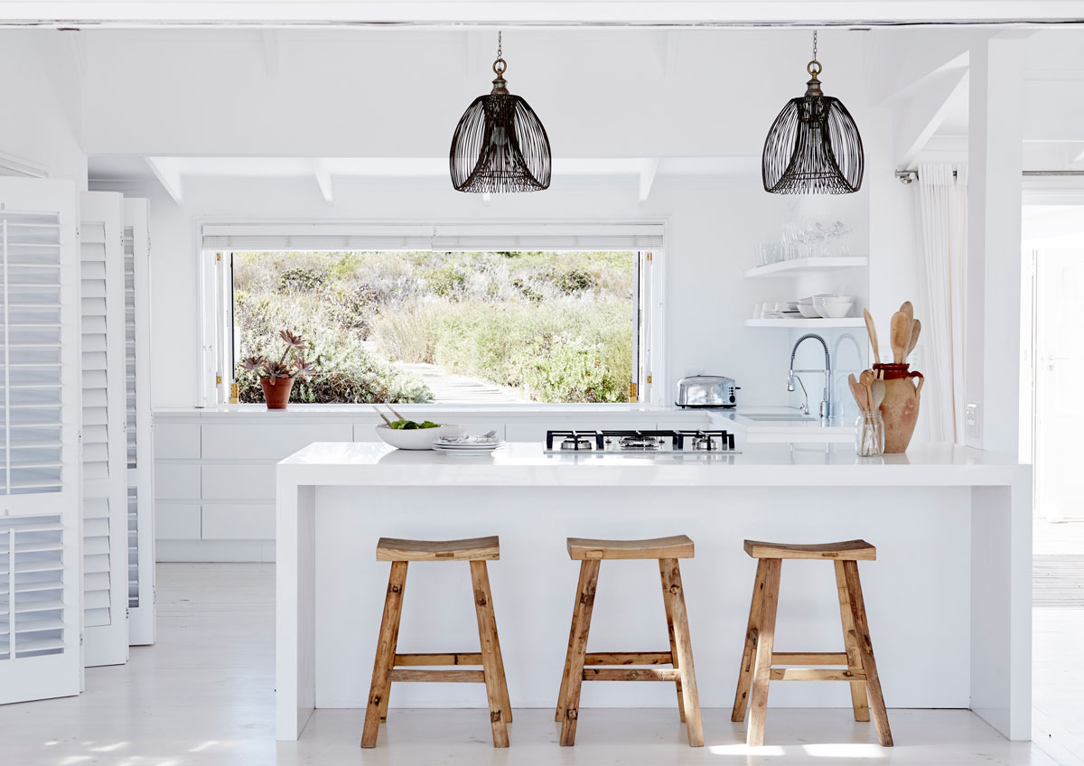 The view of the vegetation is perfectly framed by the new kitchen window that can be opened up completely. The house takes cues from the natural surroundings for textures and materials.