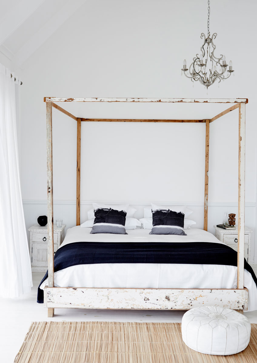 The four-poster bed of distressed, salvaged wood looks like it might have washed ashore. Here leather, woven grass, rough woven linen and luxurious cotton happily cavort.