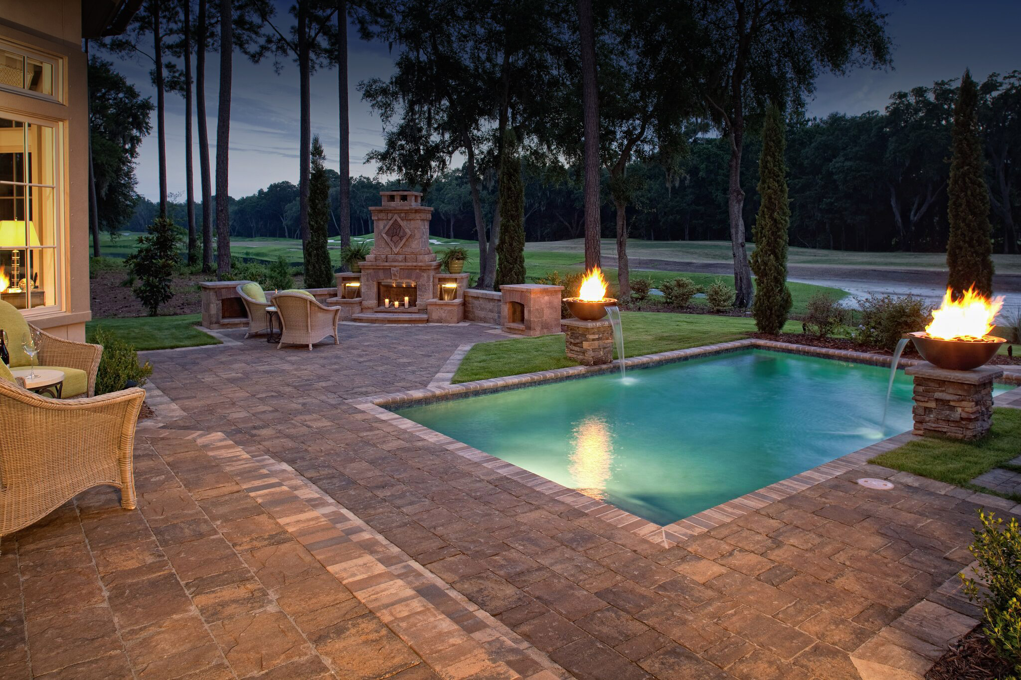 The warm paver design for both the patio and pool deck of this home allows the design to easily flow from one outdoor space to the next. We offer a variety of copings and cap units that can be used for trim. If you look closely at the project above you'll notice we used the same trim for the steps and around the landscape to create a final polished, cohesive look.