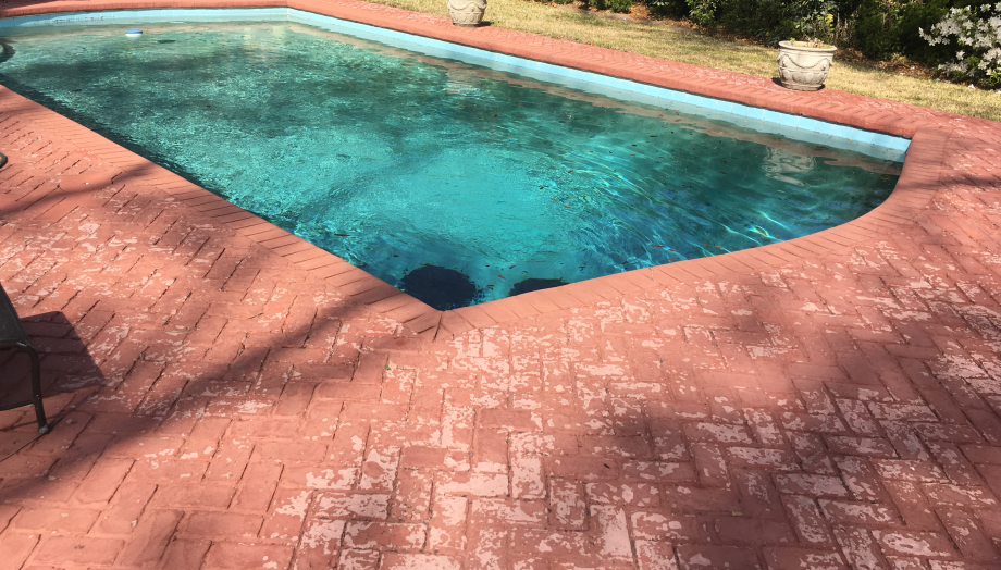 BEFORE: The pool deck before the paver remodel was faded, worn, and cracked.