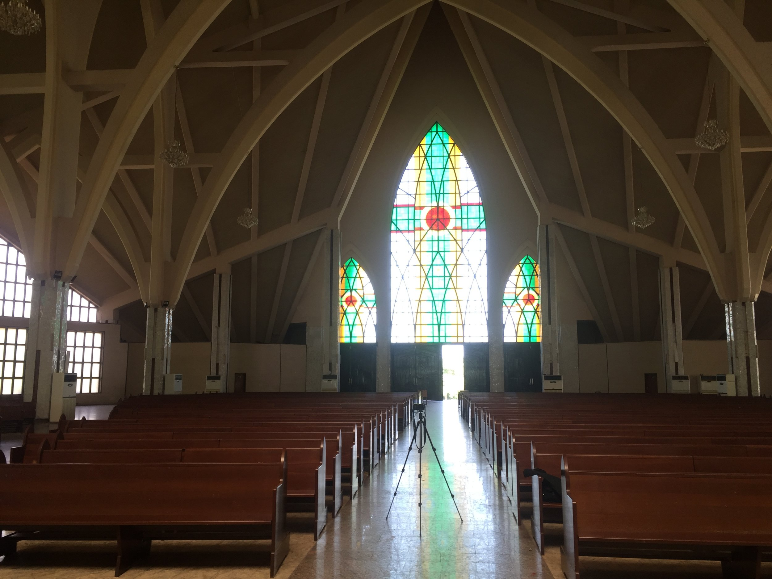A complete view of the church with the stained glass windows mixing the colors green, red, and yellow to create a beautiful scene with natural light penetration.