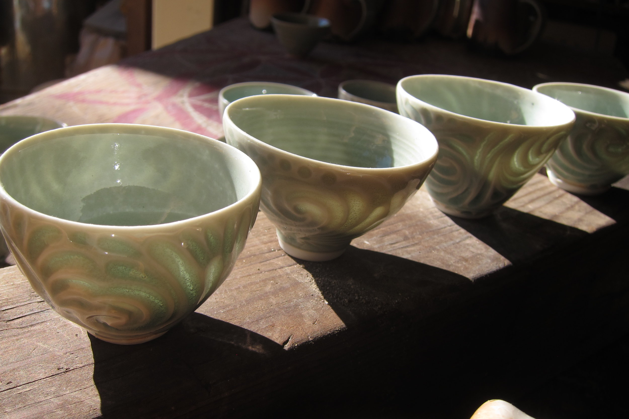 Carved porcelain tea cups showing off their translucency.
