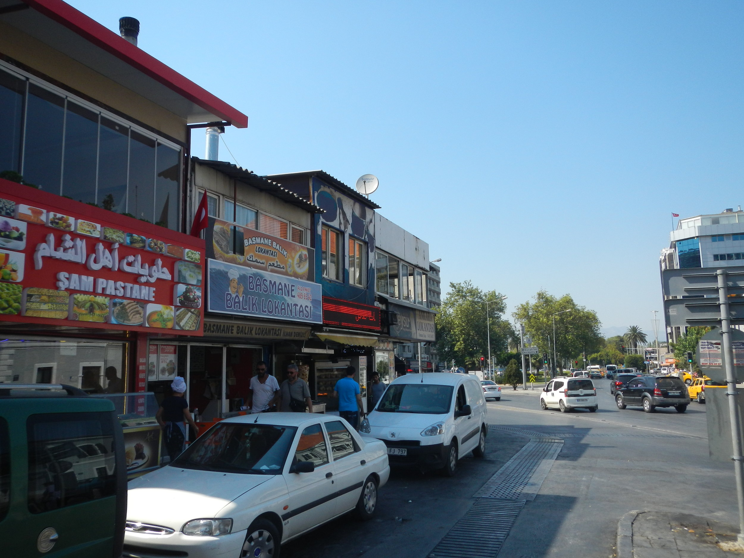 Basmane has been transformed by its Syrian population. This is the main square, with a Syrian sweet and food shop, a Turkish seafood restaurant and a Syrian shawarma shop all displaying their names in Arabic and Turkish. Further down the road are Syrian and Turkish barber shops, vegetable stalls, tea and shisha cafes, electronics stores, and clothing shops.