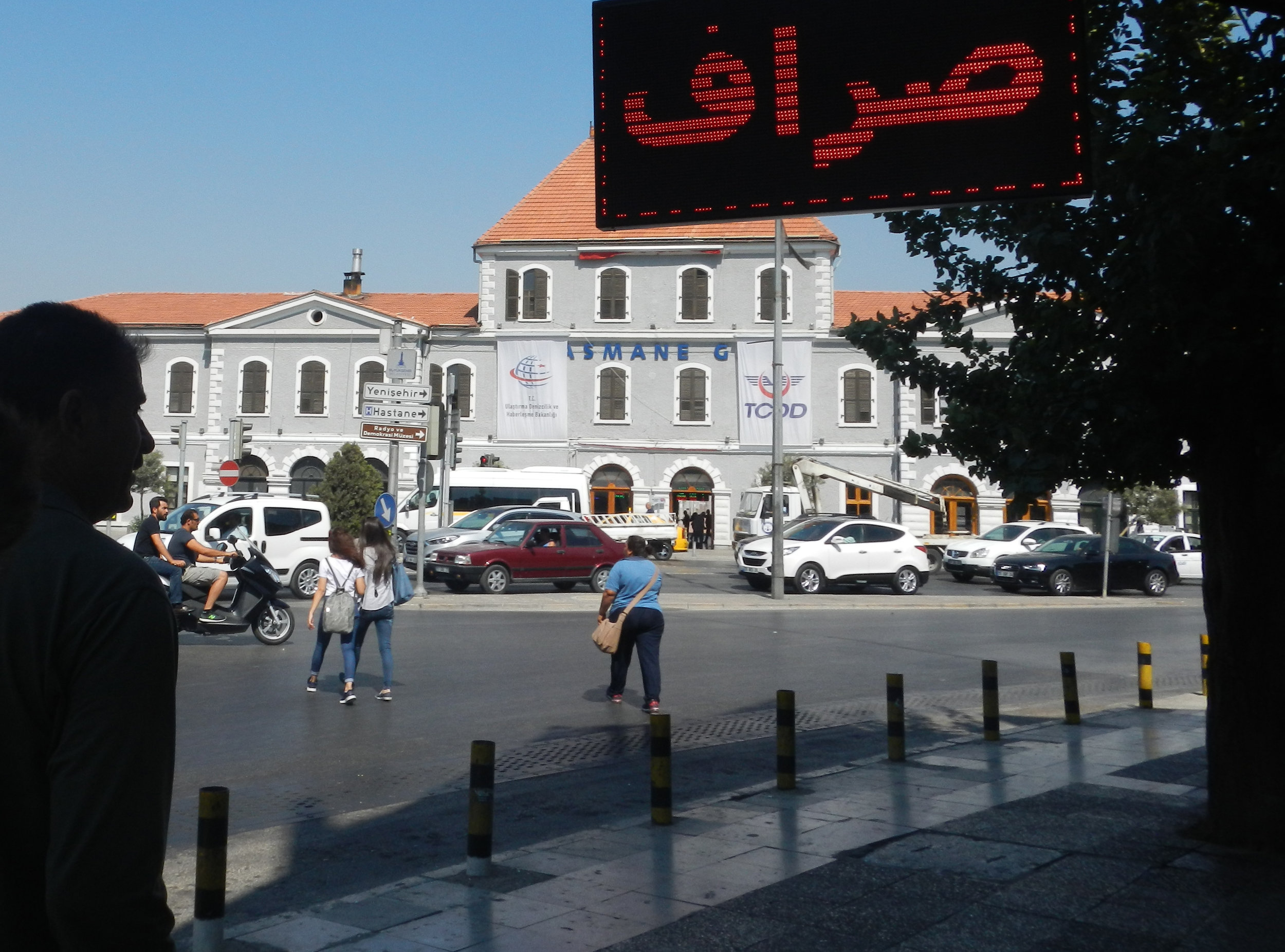 An Arabic sign advertises a  saraf , or money transfer shop which sends funds across the Arab region, Turkey, and Europe through informal networks. In the background is Basmane Gari, the train station that gives the neighborhood its name.