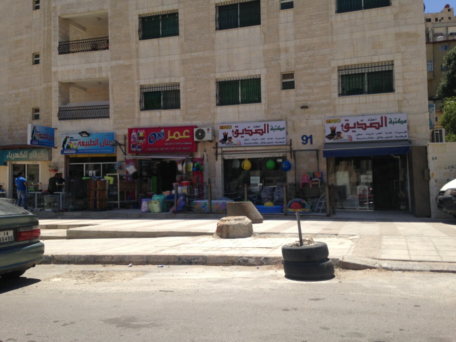 Typical low-to-middle-income apartments in Amman, sitting above a line of storefronts.