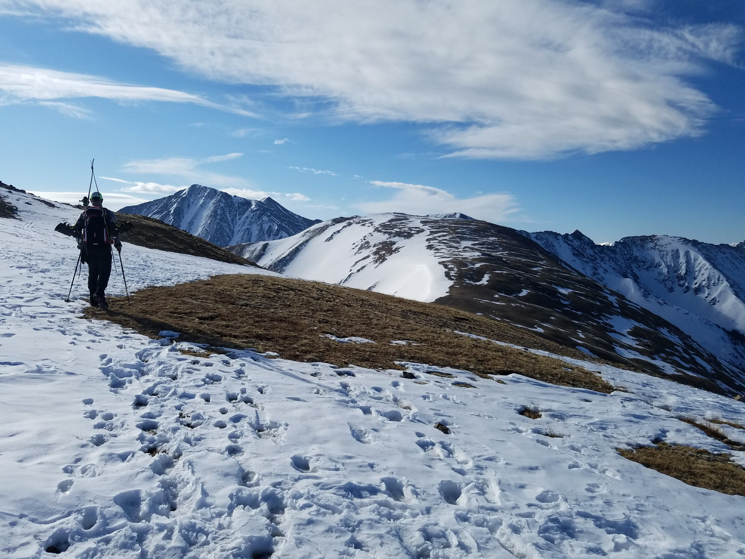 Hiking along the continental divide. Cupid (13,117') is the rounded bump ahead of us, and Torrey's Peak (14,257') is the tall mountain beyond, left of center. The upper tines of Tuning Fork are visible coming off Torrey's summit ridge, just to the right of the hiker (Dad).     Photo: Mike Hasse