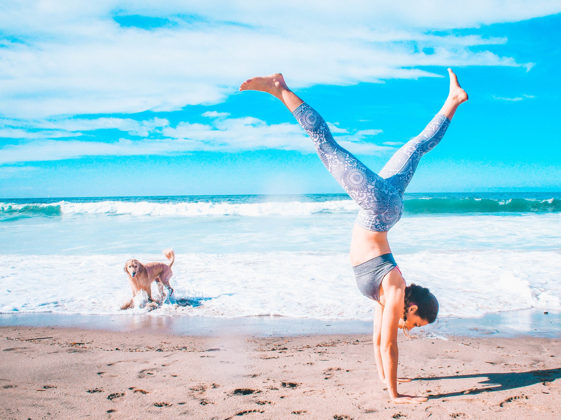 A woman plays in handstand on a beach with a brown dog in the background