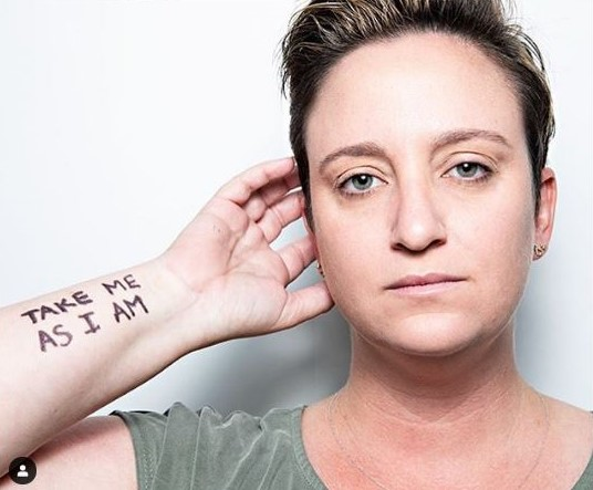 """A white woman with short brown hair looks at the camera. """"Take Me As I Am"""" is written on her arm."""