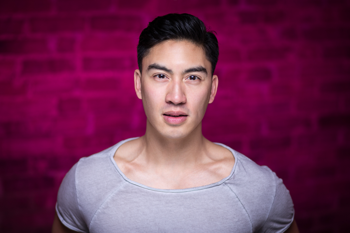 A strong headshot of energetic actor Devin Ilaw - hot pink blast