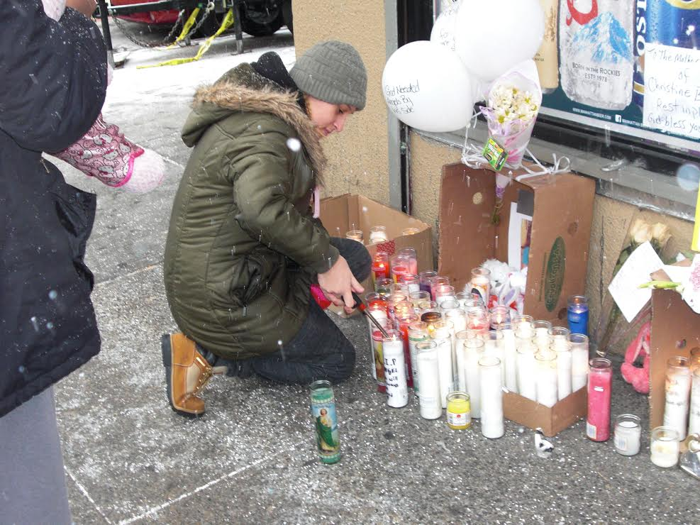 Woman lights candle for those killed in fire.
