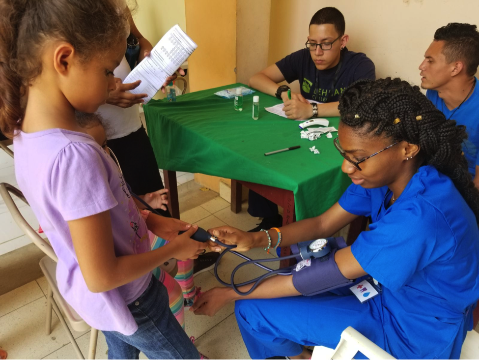 Spence with a young girl in the triage, who wanted to know how the sphygmomanometer works. And Spence allowing the young girl to test the instrument on her.
