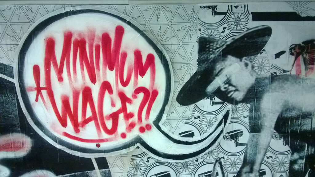 "Street art in Singapore reads ""Minimum Wage?!"" Photo courtesy of Flickr."