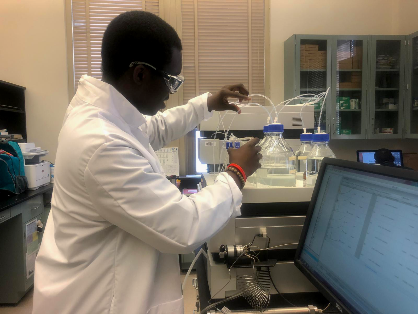 Ezekiel Olumuiyide working with a High Performance Liquid Chromatography machine. Photo by Beauty Kolade.