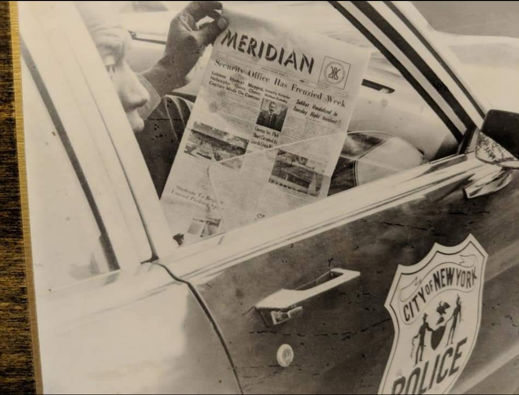 A police officer who chased a suspect on campus reading about his exploits in the Meridian. Photo by Victor Maggiolo, Meridian Editor in Chief in 1972.