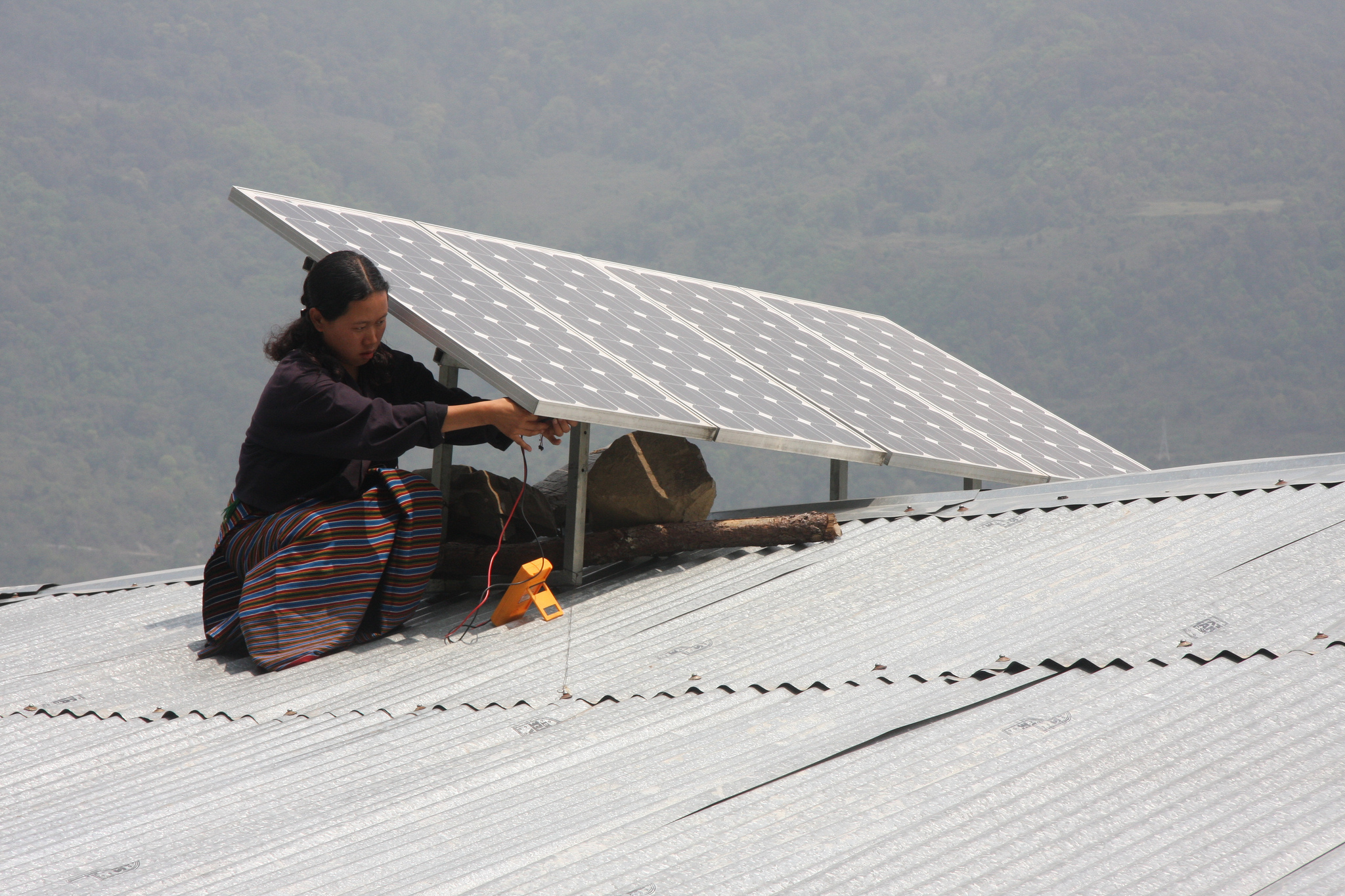 A woman installing solar panels on the roof in Bhutan. Photo by  Asian Development Bank
