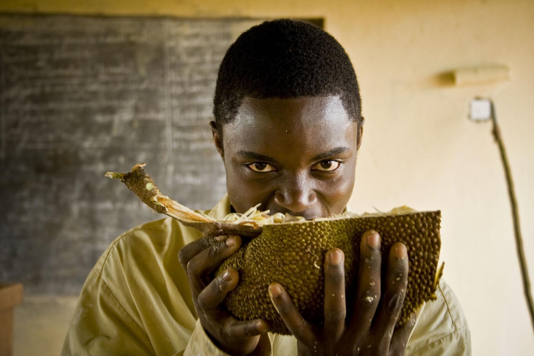 Thomas bites into a fresh jackfruit during his painting break (Nantwalla village, central Uganda)