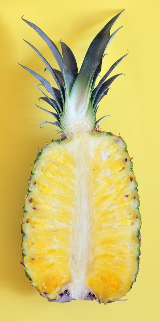 raw-cut-pineapple-on-yellow-surface-table-picture-id680957848.jpg