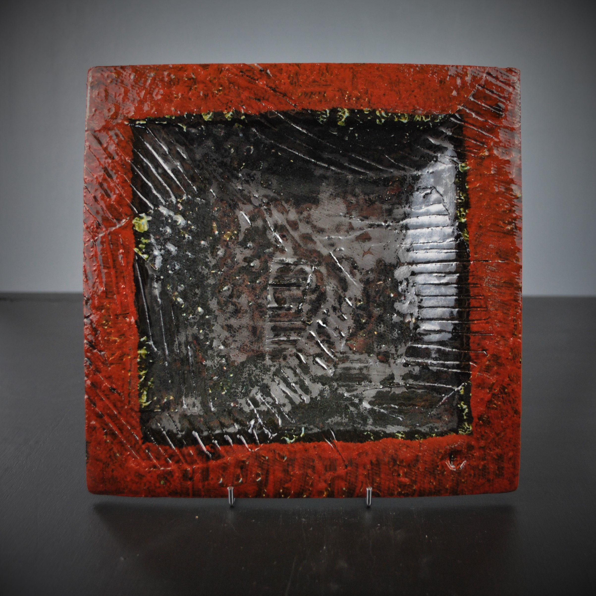 Dave Harper SQUARES series.  2019 Shallow slipware plate 2018. (Orangy red with grey centre) on stand square edit. DSC_6329 (2).JPG