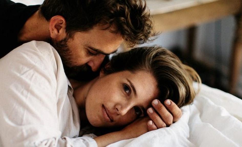 man-whispering-woman-bed.jpg