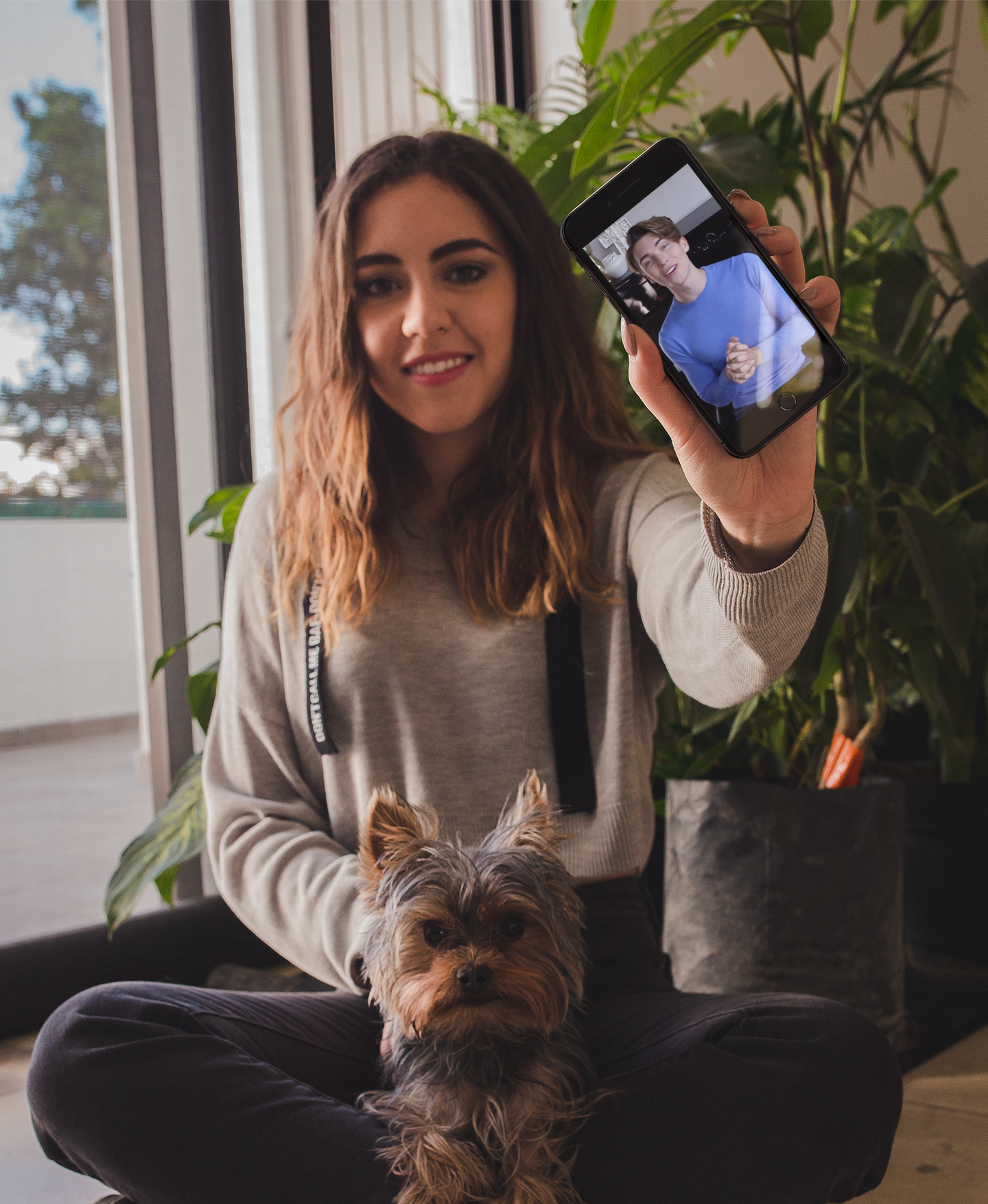 woman-sitting-with-her-dog-holding-a-black-iphone-mockup-a19639.png