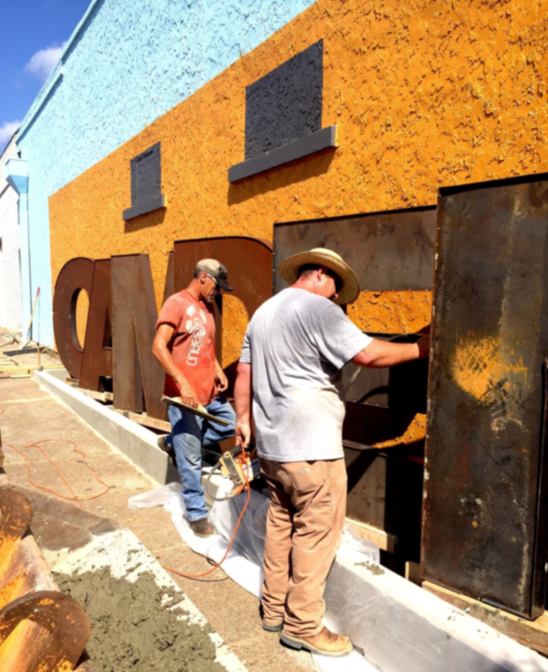Ron McCann (right), and crew member installing sculpture.