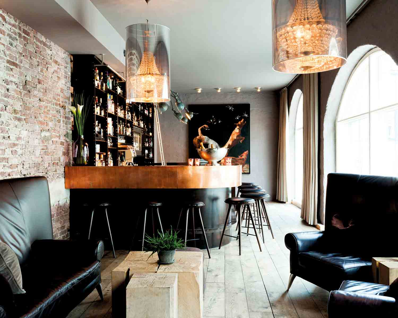Hotel Brosundet Bar Ålesund Norway, Bronze bar and raw brick wall with modern chandeliers , interior design by GARDE. Mads Emil Garde