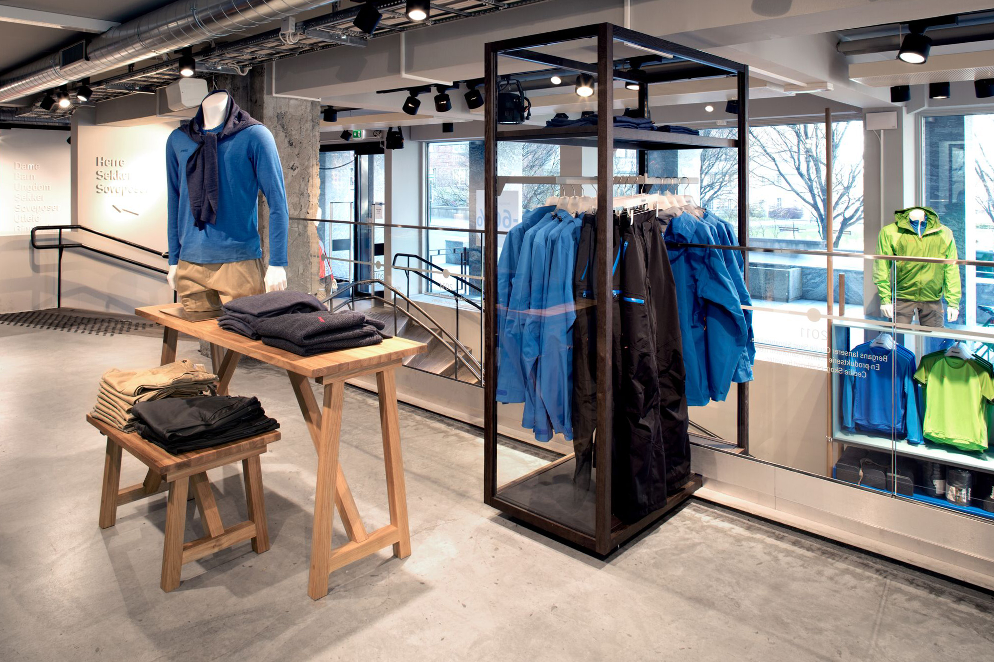 Bergans of Norway: Modern Scandinavian Flagship Store, done with rustic concrete floors, minimalist wood furniture and shelving, made to compliment the vibe of the outdoor brand - Interior Design by GARDE. Mads Emil Garde