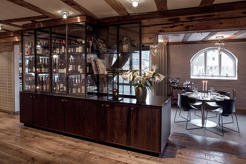 Hotel Brosundet Restaurant Ålesund Norway, raw dark wood and glass wine cabinets , interior design by GARDE. Mads Emil Garde