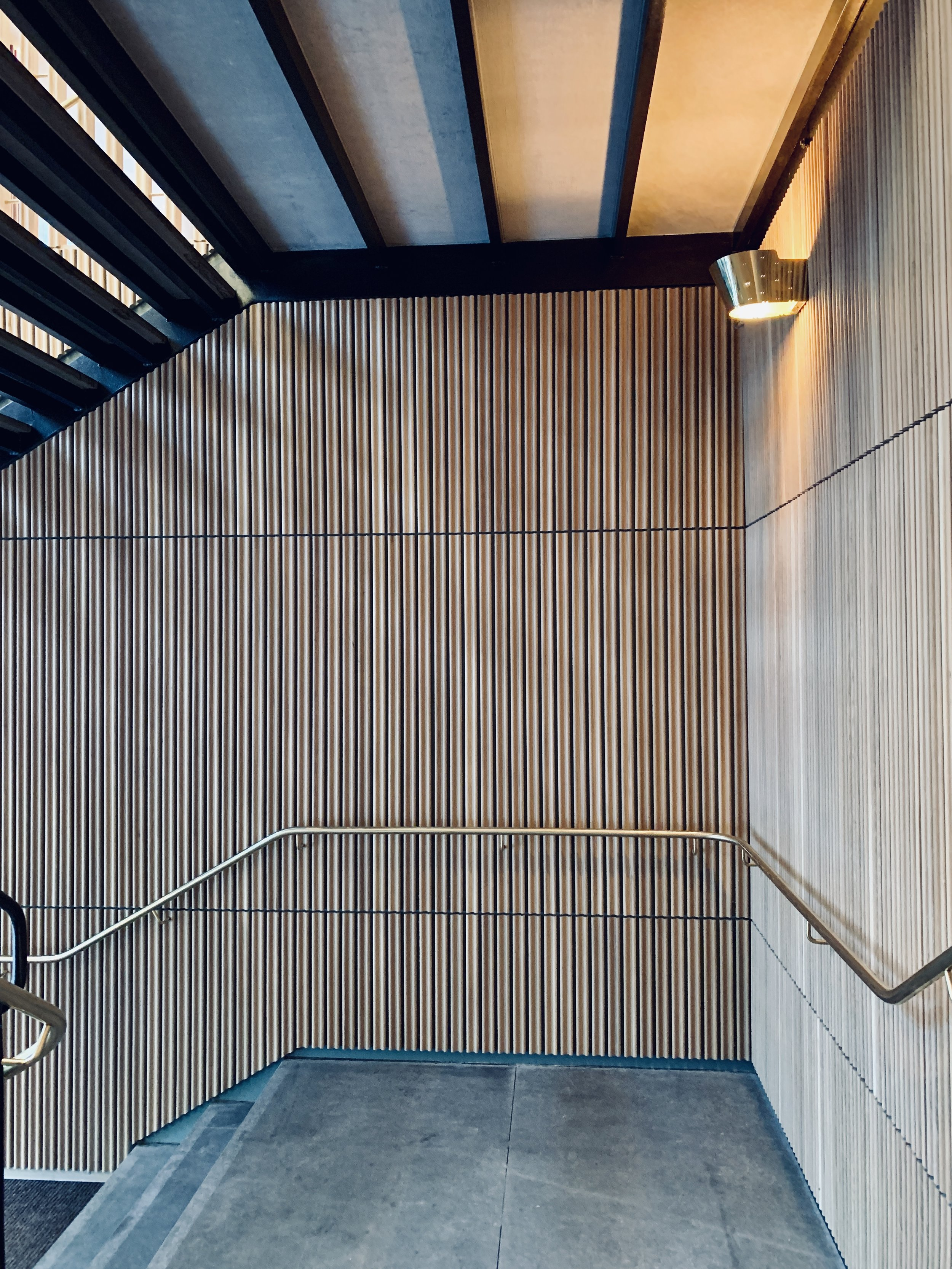 Restaurant Tivander architect drawn concrete staircase, brass hand railing and lighting