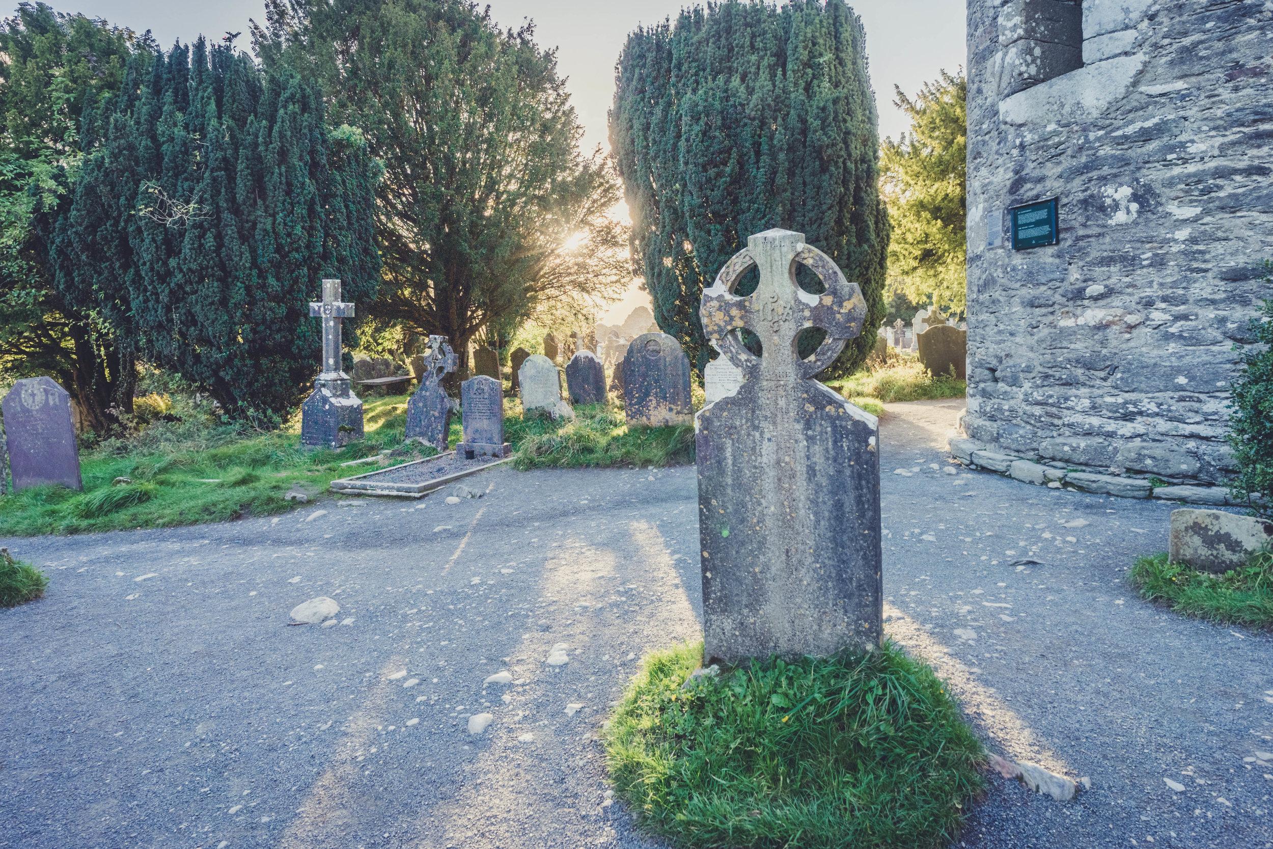 glendalough. irish history. county wicklow. round tower. hill walknig. hiking. grave yard. wildlife. tombstones. lakes. blue sky. head stones in the sun.jpg