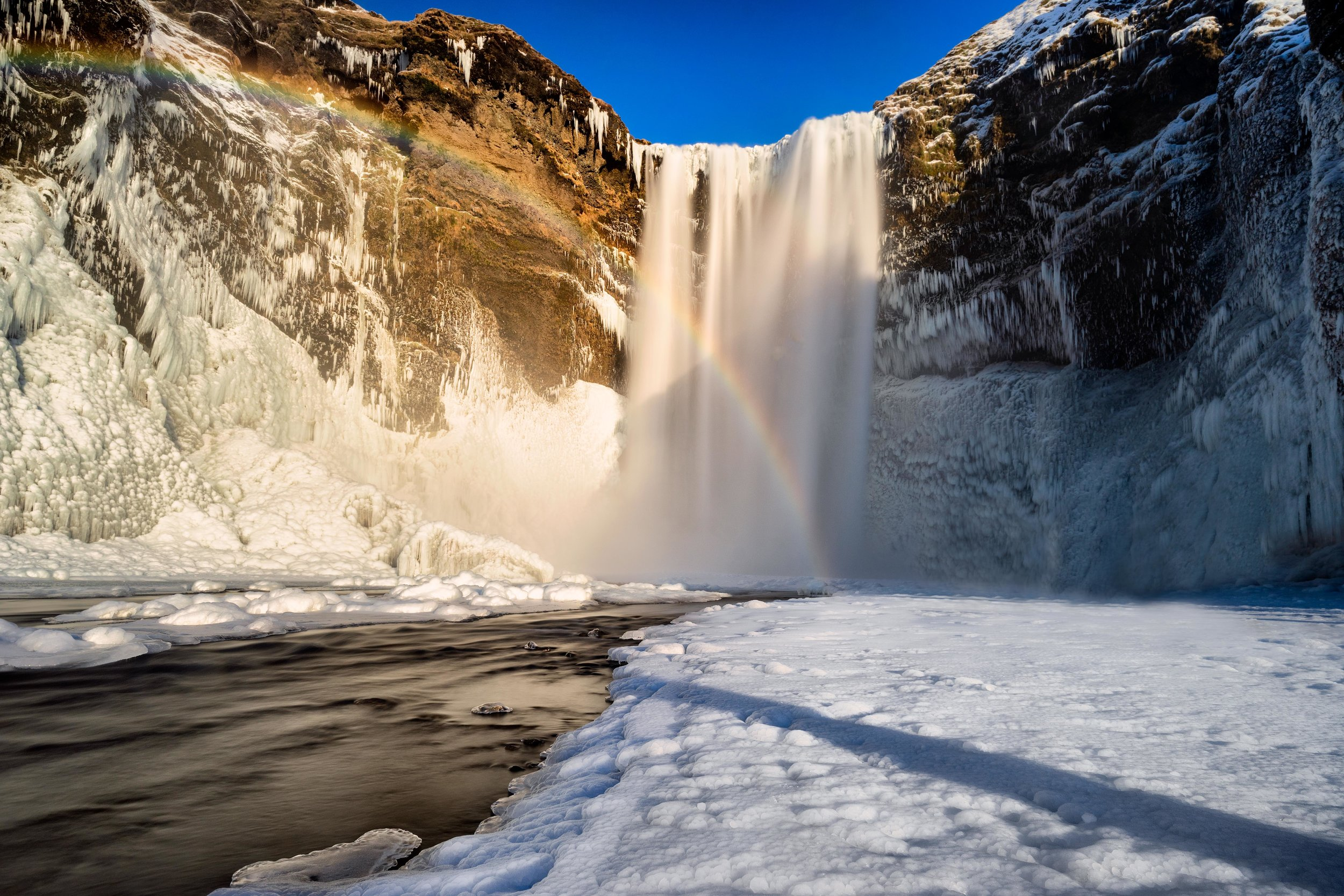 Iceland. snow. travel. adventure. photography. trip. epic landscape. snow. cold. freezing. sunrise. epic waterfall with rainbow.jpg