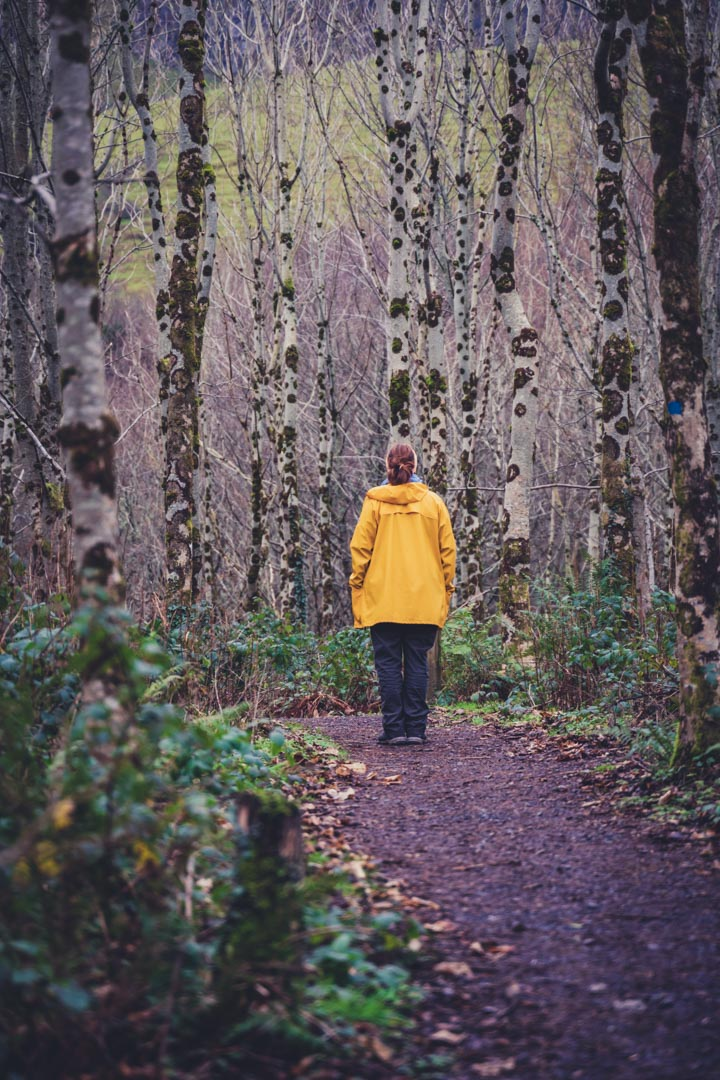 girl in yellow jacket standing in forest
