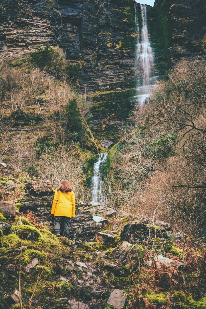 girl in yellow jacket standing near waterfall