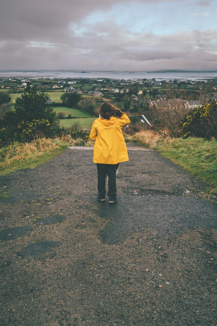 girl in yellow jacket overlooking beach