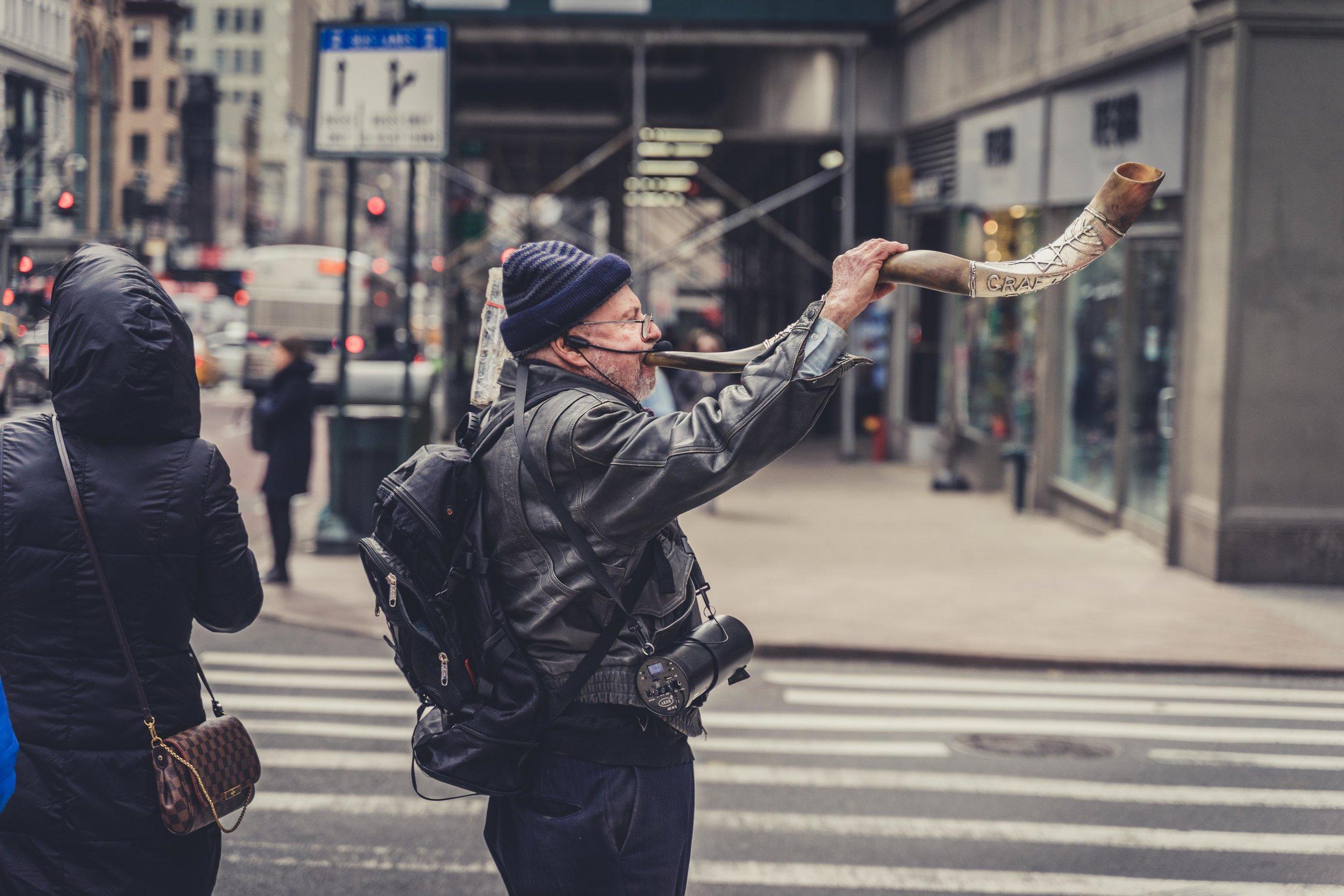 new york city streets man blowing a big horn.jpg