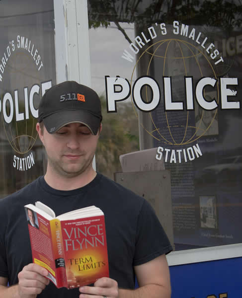 Daniel-the-smallest-cop-reading-by-the-smallest-police-station.jpg