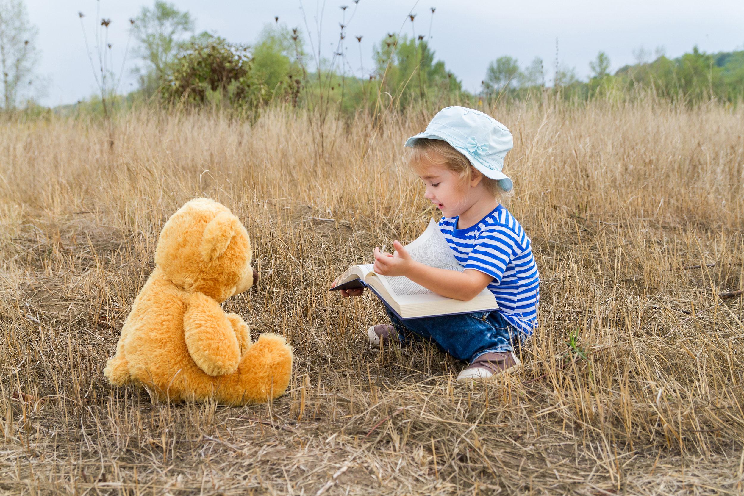 Girl reading to teddy.jpeg