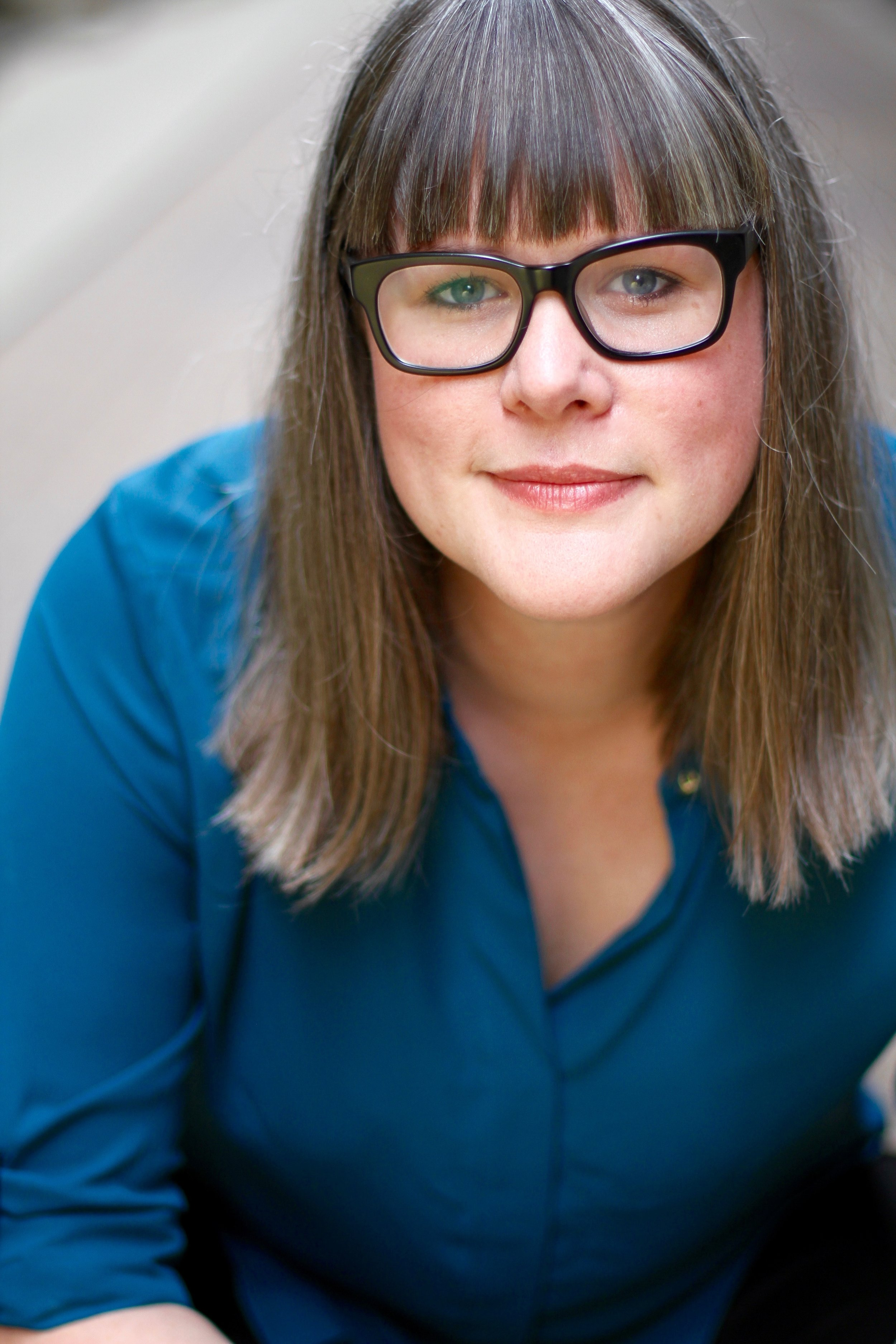 headshot of Bridget Melton: image of woman seated with straight hair, eyeglasses and a teal collared shirt.