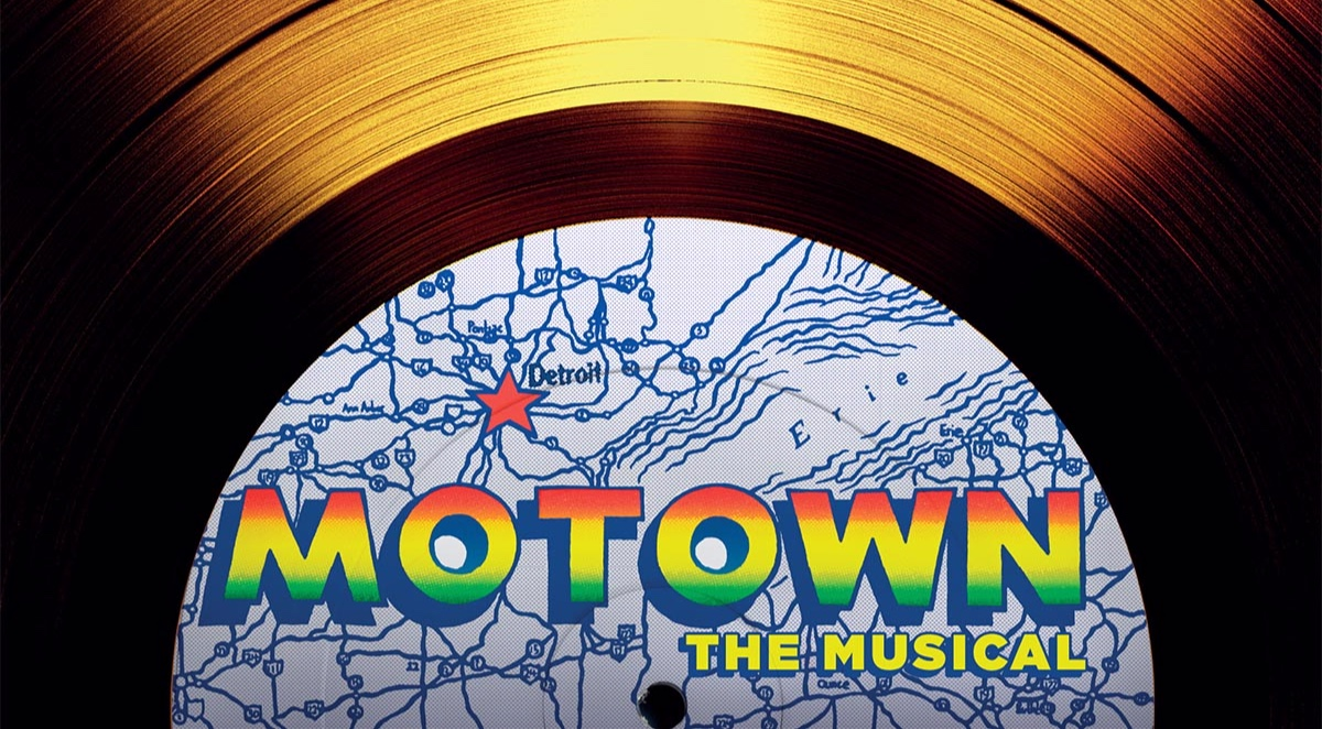 "Image description: detail photograph of a gold record with the center label partially shown. Center label text reads ""Motown"" in ombre letters of red, yellow, and green, and underneath in yellow text ""The Musical"". Background is light blue map of Michigan with roads marked in dark blue and a red star over Detroit."