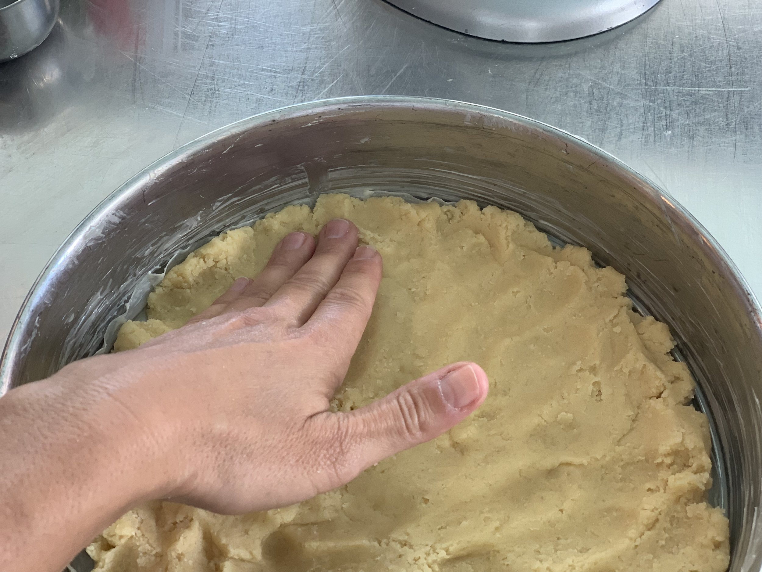 The dough is being firmly pressed into the bottom of a greased 9-inch springform pan.