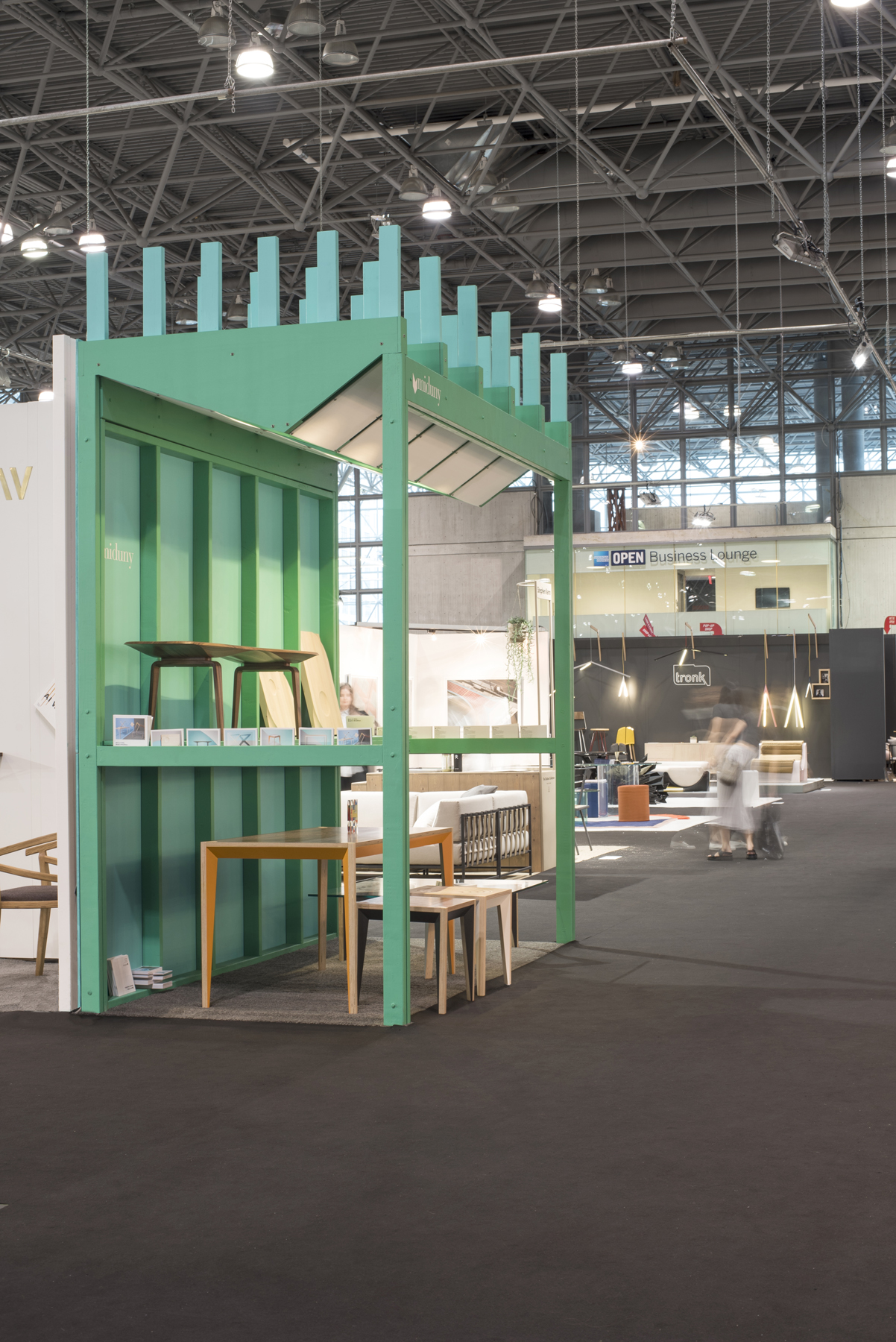 The booth, designed by alepreda architecture, has integrated lighting and slots at the sides to place postcards and pamphlets.
