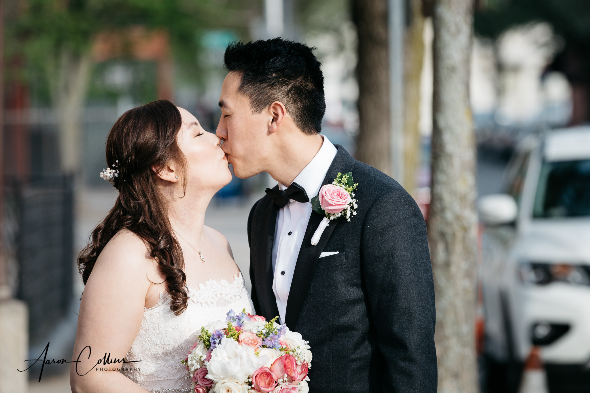 Bride and groom share a kiss on the street in cambridge