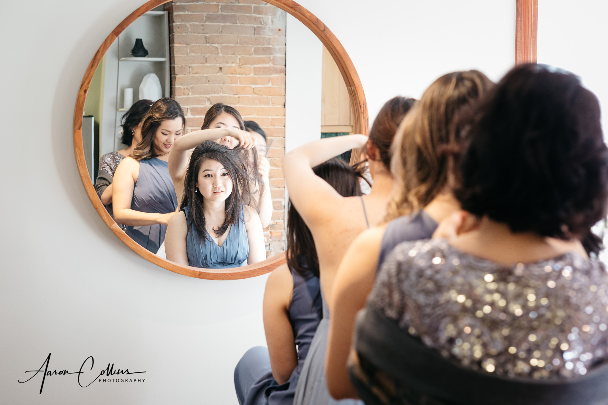 Five people using one mirror as the bridesmaids amd mother of th