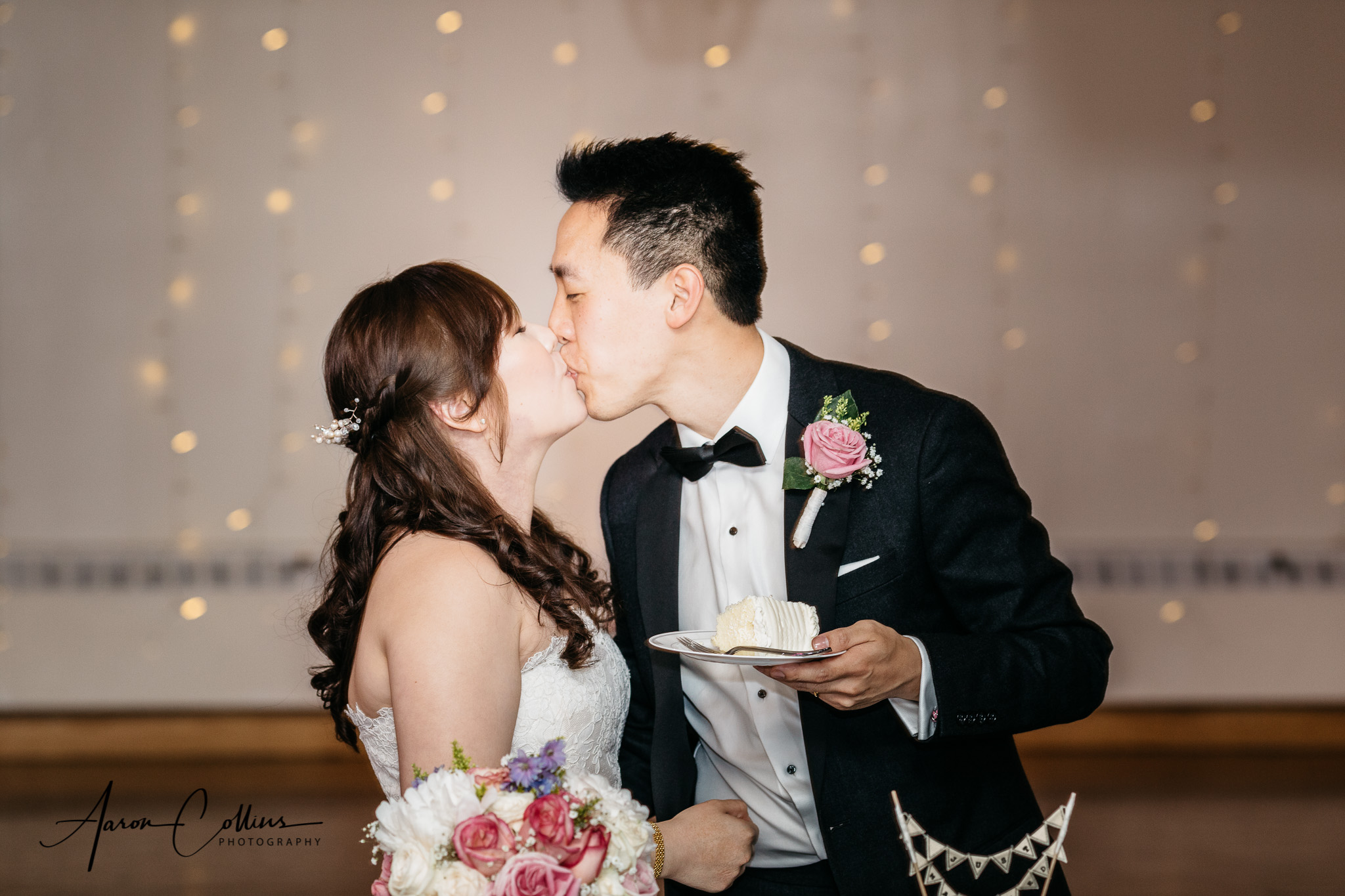 Bride and groom cutting the cake and sharing a kiss