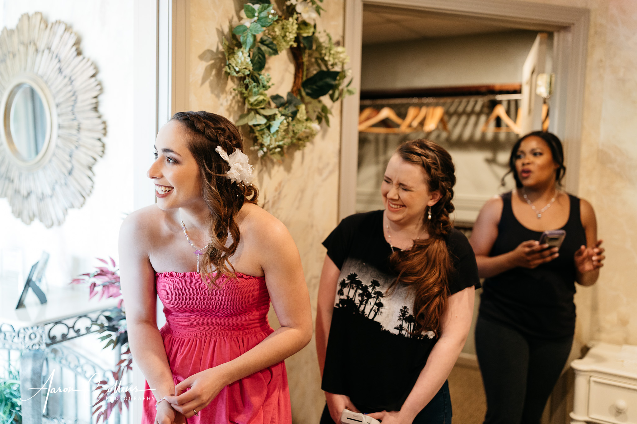 The bride and her entourage of bridesmaids in the bridal room at A Villa Louisa laughing as they wait for a friend to arrive for the wedding.