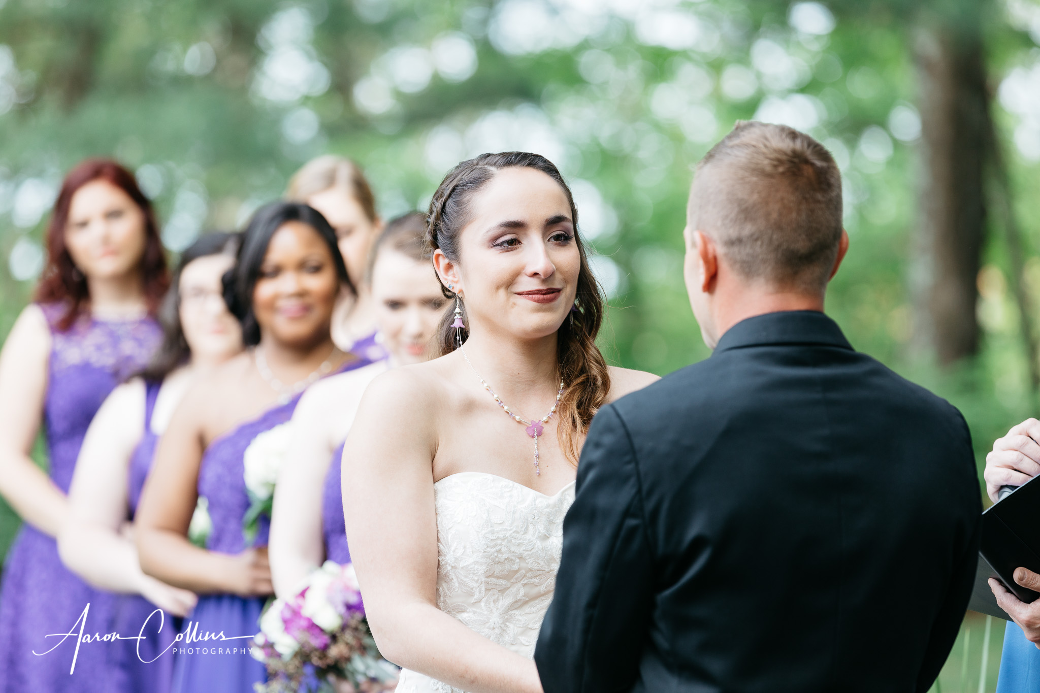 A bride with her bridesmaids looking on as she hears her vows from her soon to be husband.