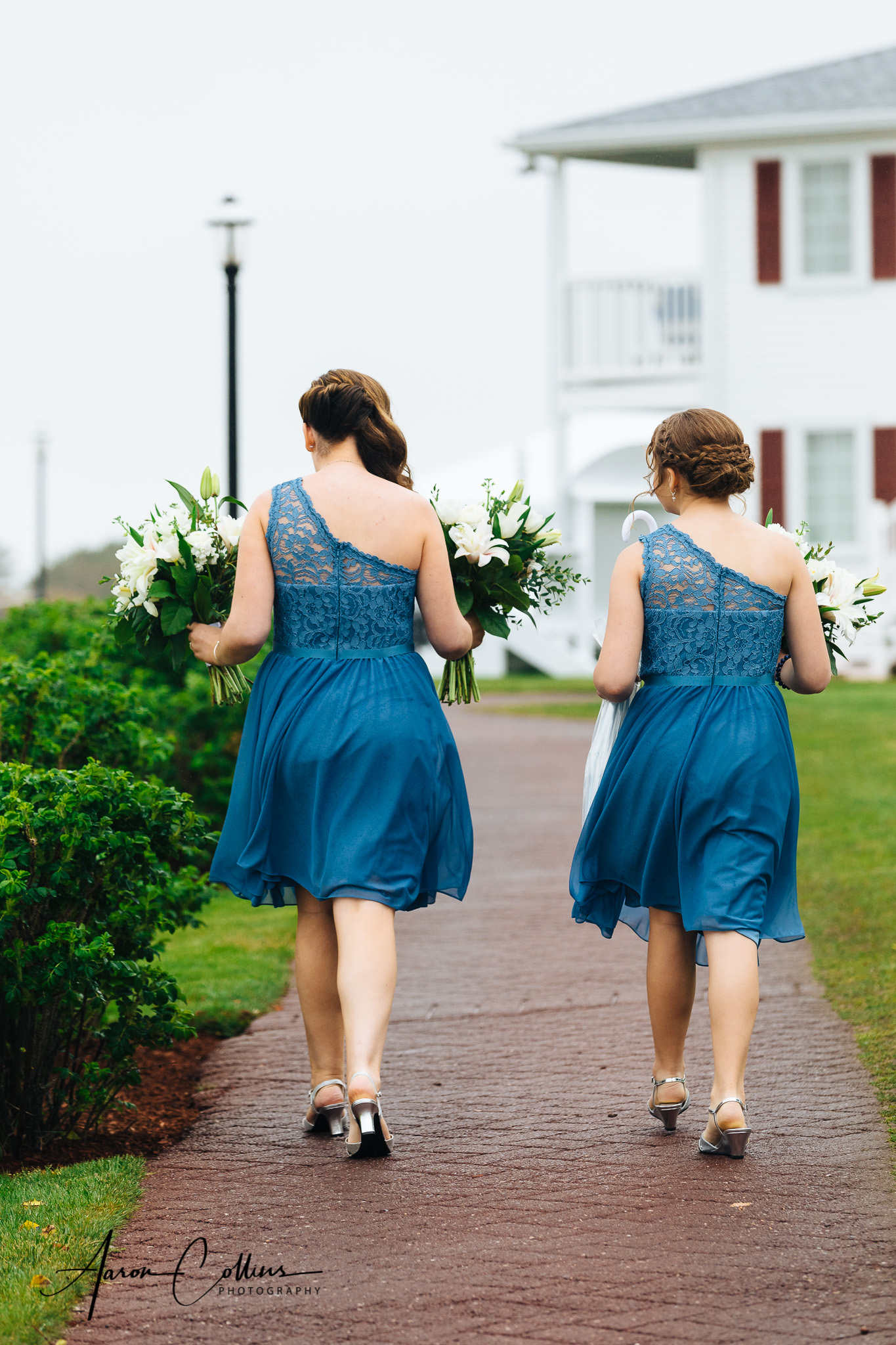 Bridesmaids walking side by side in blue on a red brick walkway