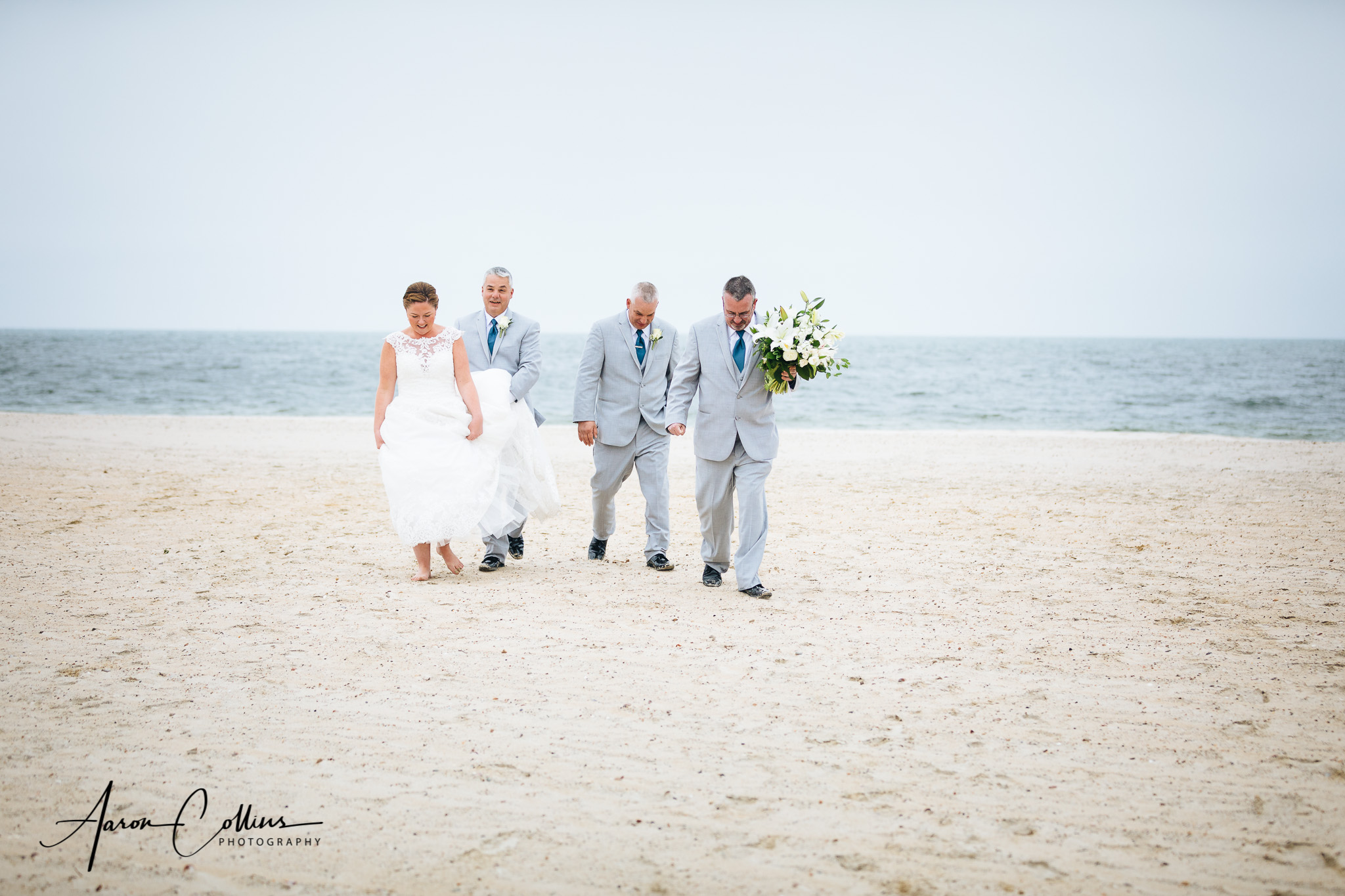 Groomsmen helping the bride keep the sand off her dress on the beach.