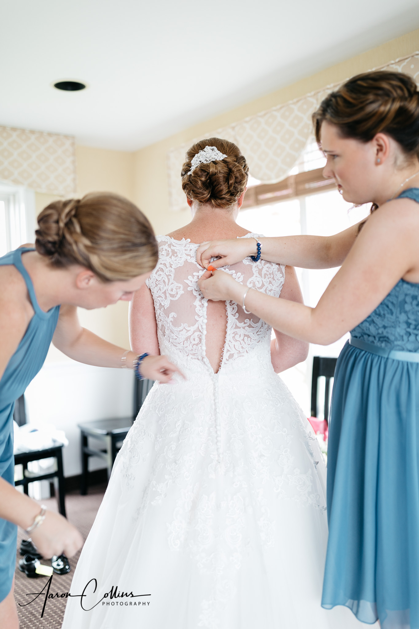 Bridesmaids helping the bride button up the back of her wedding dress.
